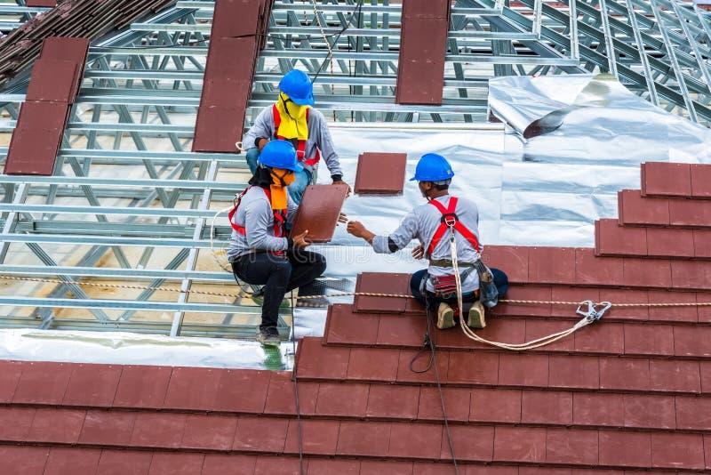 Los trabajadores están en el marco de acero para las nuevas tejas de techumbre imagen de archivo libre de regalías
