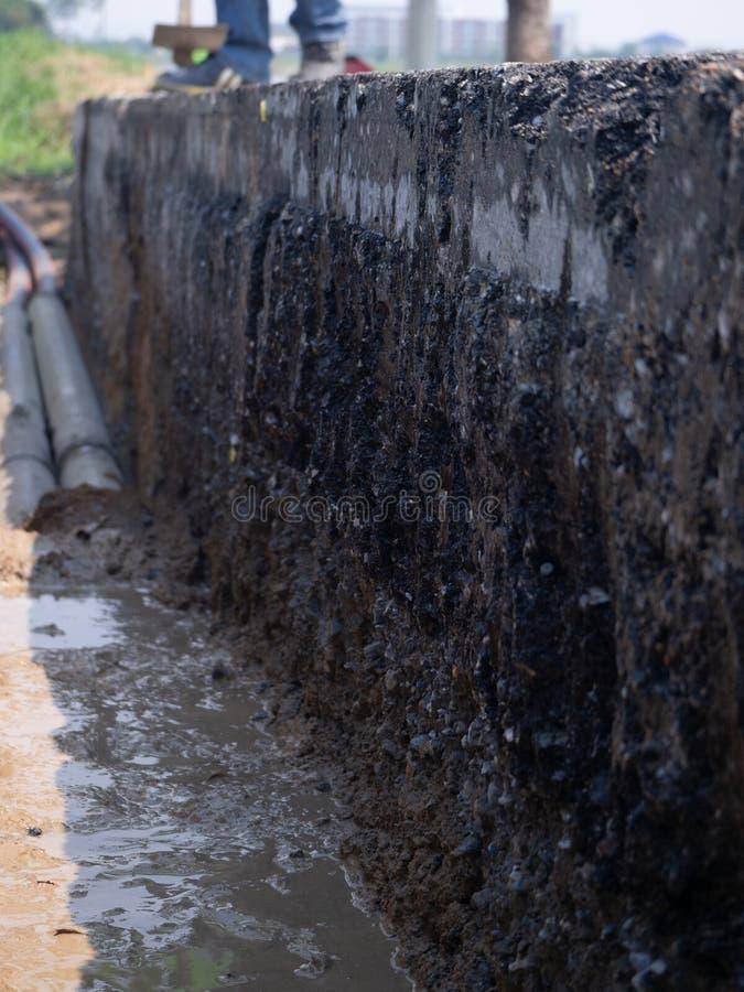 Los trabajadores están instalando drenes concretos en el lado del camino foto de archivo libre de regalías