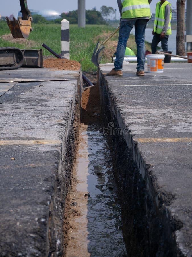 Los trabajadores están instalando drenes concretos en el lado del camino fotos de archivo