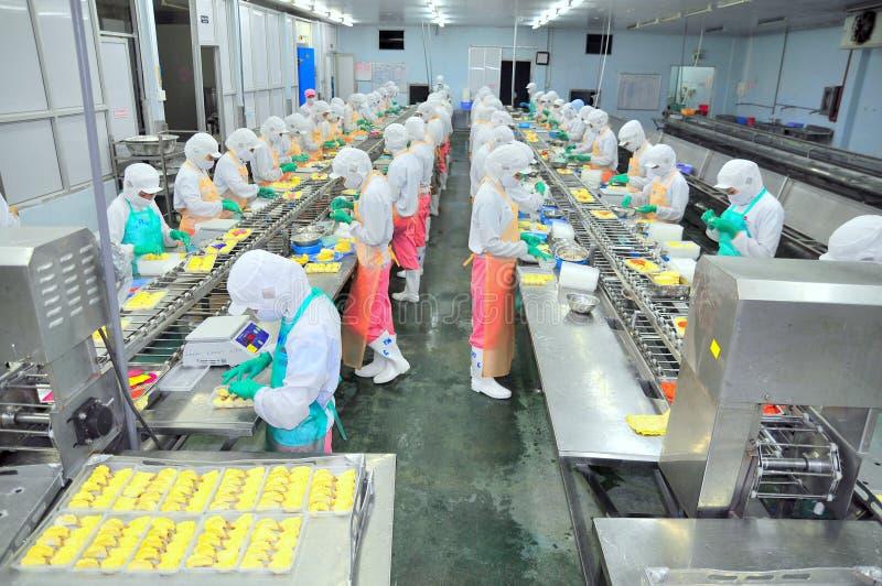 Los trabajadores están trabajando difícilmente en una cadena de producción en una fábrica de los mariscos en la ciudad de Ho Chi  imagenes de archivo
