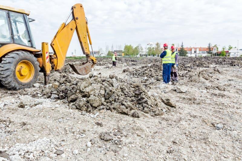 Los trabajadores están trabajando manualmente al lado del excavador, trabajo en equipo, mA foto de archivo libre de regalías