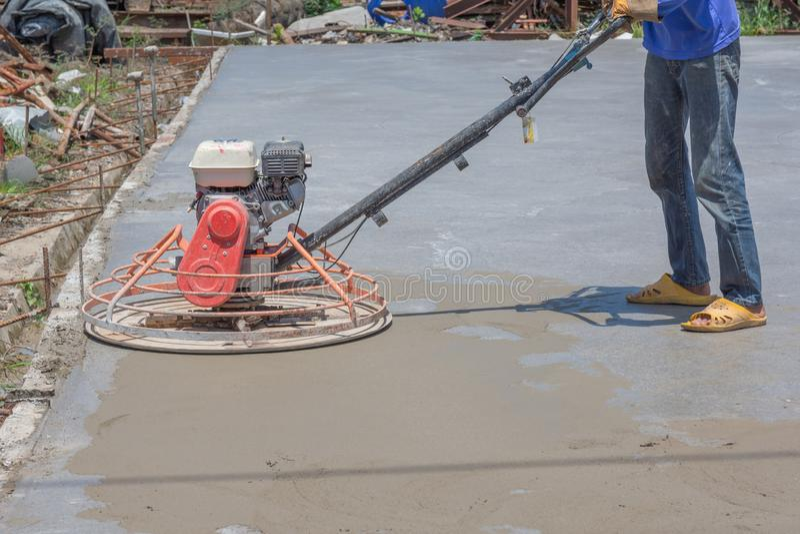 Los trabajadores están utilizando las máquinas pulidoras concretas para el cemento después de verter el hormigón preparado fotografía de archivo