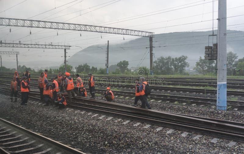 Los trabajadores ferroviarios en chalecos anaranjados están reparando pistas imagenes de archivo