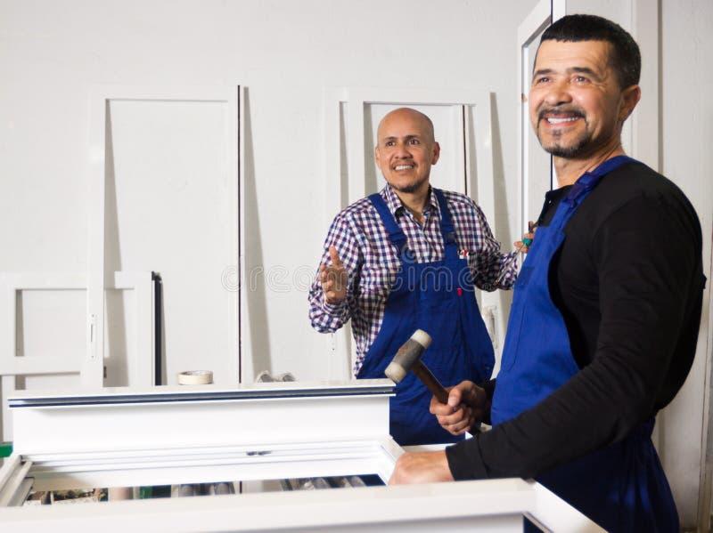 Los trabajadores hacen el marco de ventana foto de archivo libre de regalías