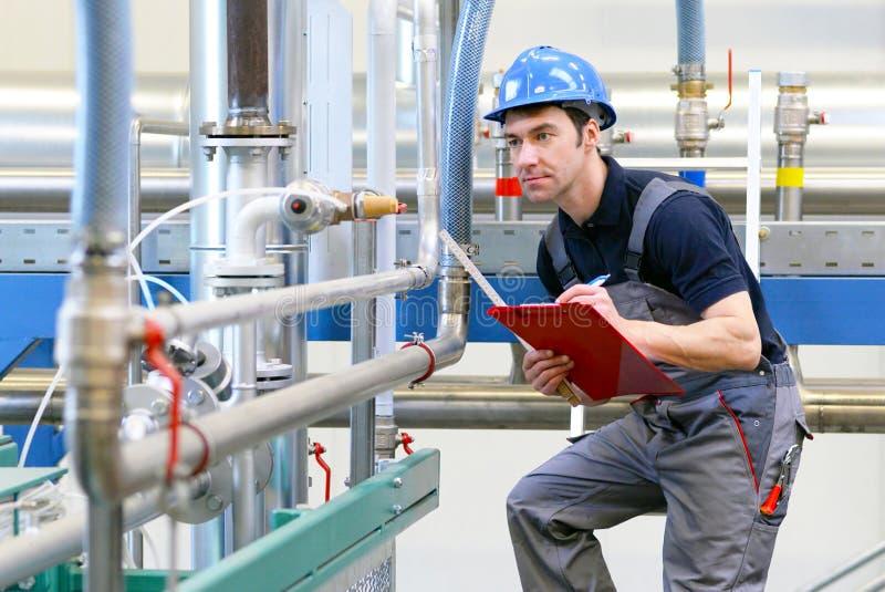 Los trabajadores industriales examinan la tecnología de una planta para saber si hay functio fotografía de archivo