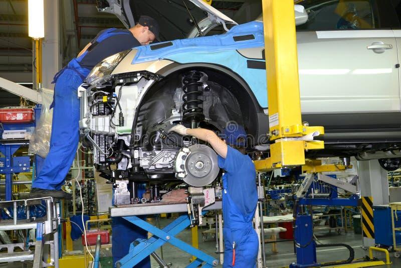Los trabajadores instalan el motor en el coche Línea de montaje del auto imágenes de archivo libres de regalías