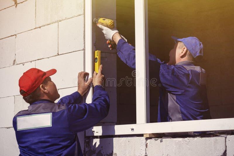 Los trabajadores instalan la reparaci?n de construcci?n pl?stica de las ventanas imagen de archivo