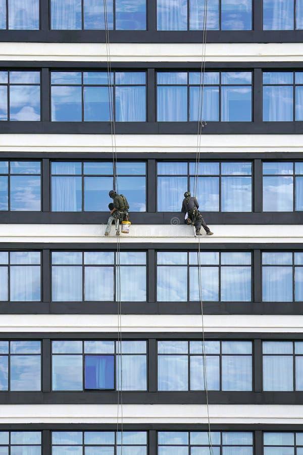 Los trabajadores limpian las ventanas en los rascacielos fotografía de archivo