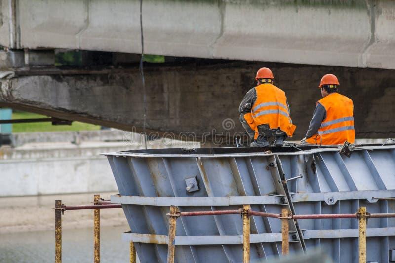 Los trabajadores montan la estructura del puente y de la gente sentados el resto imágenes de archivo libres de regalías