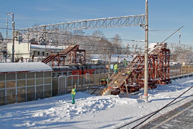Los trabajadores montan un puente de arriba temporal sobre el ferrocarril en Vidnoe imagenes de archivo