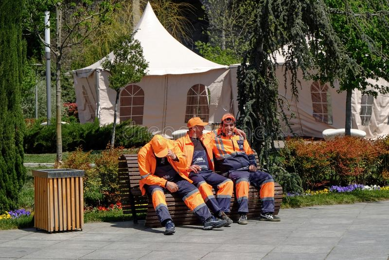 Los trabajadores municipales de la ciudad se están sentando en un banco para el breve descanso después de limpiar el día soleado  foto de archivo
