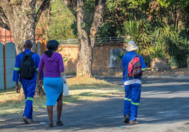 Los trabajadores negros caminan a sus trabajos en Suráfrica fotografía de archivo