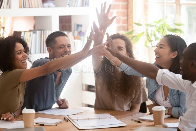 Los trabajadores o los compañeros de clase alegres sienten felices dando arriba cinco imágenes de archivo libres de regalías
