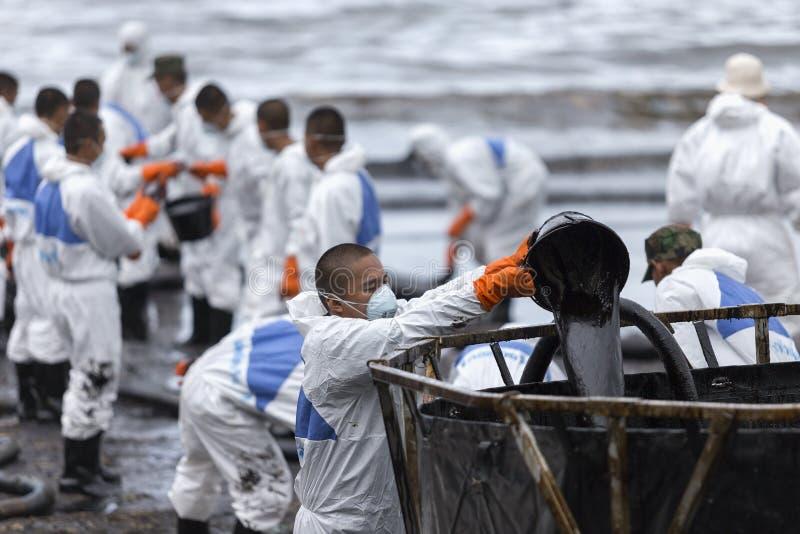 Los trabajadores quitan y limpian la bahía desbordada de Prao del petróleo crudo foto de archivo