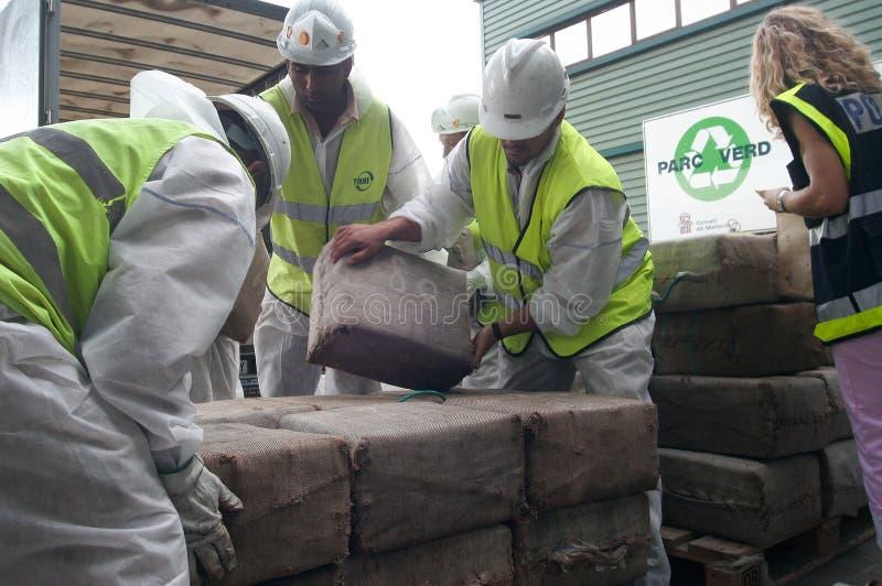 Los trabajadores recuperan paquetes de la droga de un camión antes de su destrucción fotografía de archivo