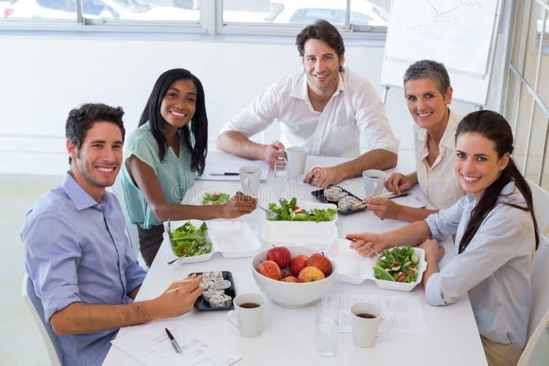 Los trabajadores sonríen en la cámara mientras que comen el almuerzo sano fotos de archivo libres de regalías