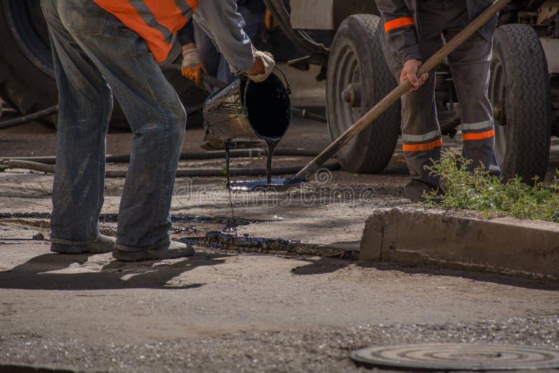Los trabajadores vierten la superficie de la carretera de la resina para cubrir el asfalto fotografía de archivo libre de regalías