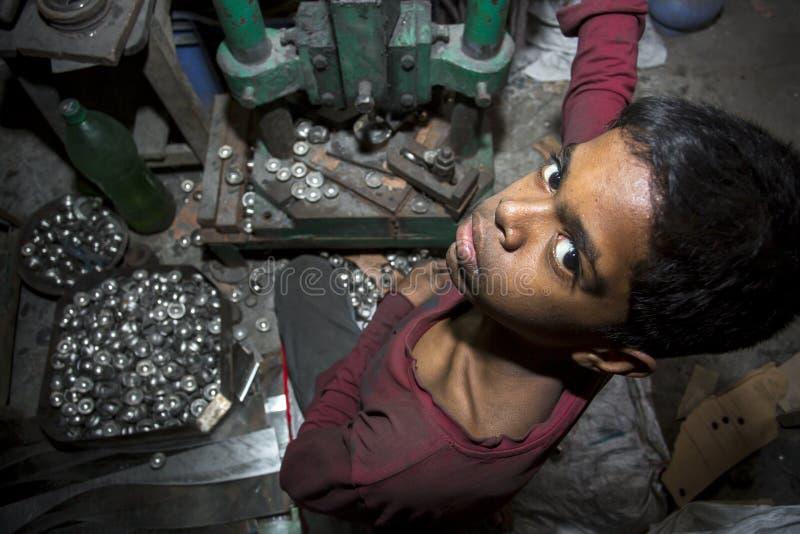Los trabajos infantiles están trabajando la bola de acero que hace la fábrica foto de archivo
