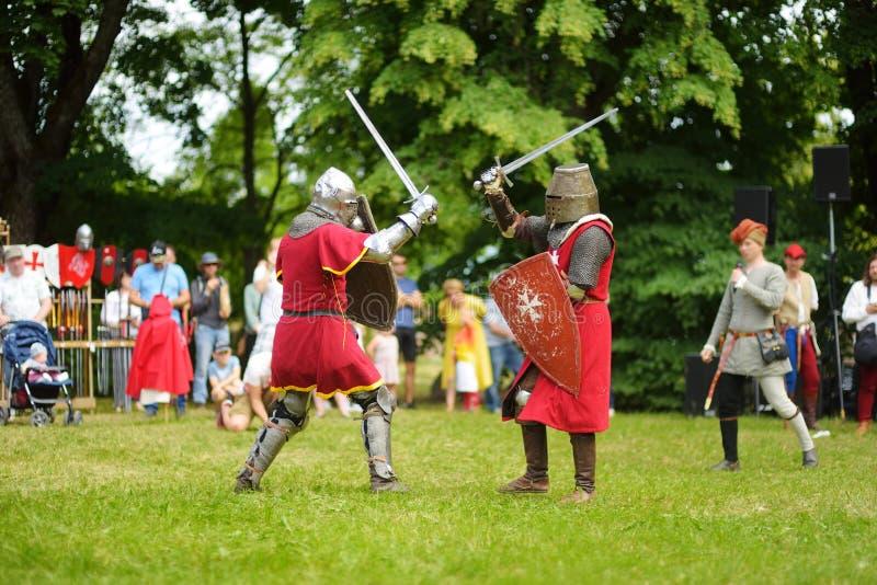 Los trajes del caballero de la gente que llevan luchan durante la reconstrucción histórica en el festival medieval anual, llevado imagen de archivo