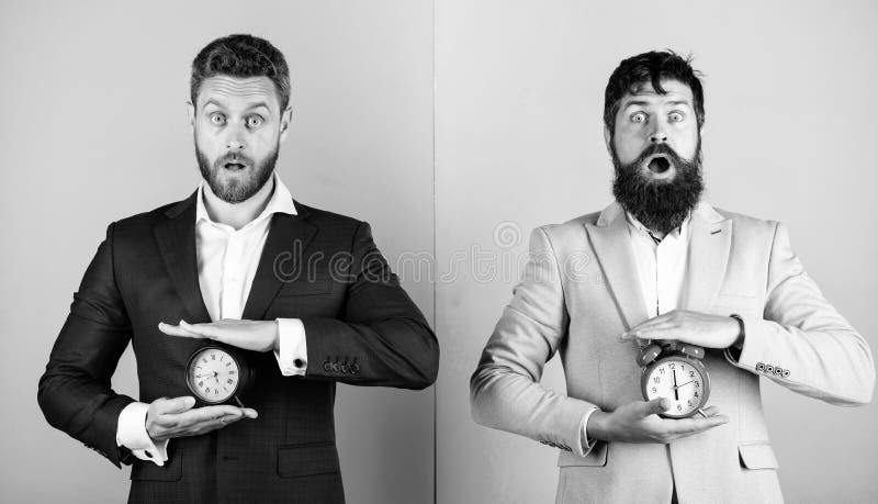 Los trajes formales del negocio de los hombres sostienen los despertadores La falta de gesti?n de la autodisciplina a tiempo llev fotografía de archivo libre de regalías