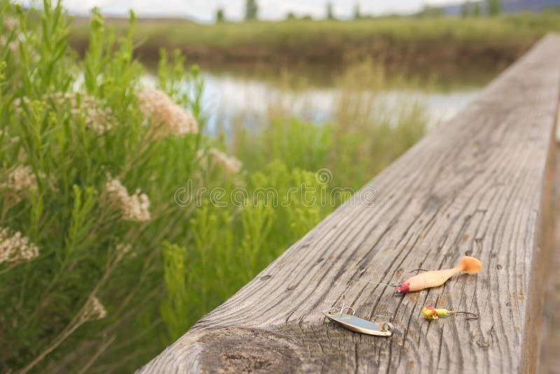 Los trastos dejados en la pesca del muelle a lo largo de la impulsión de la fauna en marrones parquean a principios de verano fotografía de archivo
