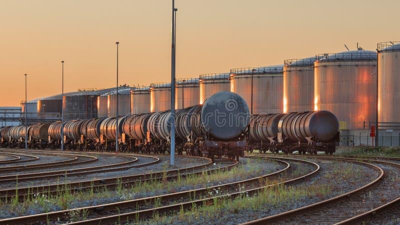 Los trenes con los silos de una planta petroquímica en el fondo se encendieron por la luz caliente, puerto de Amberes, Bélgica fotos de archivo libres de regalías