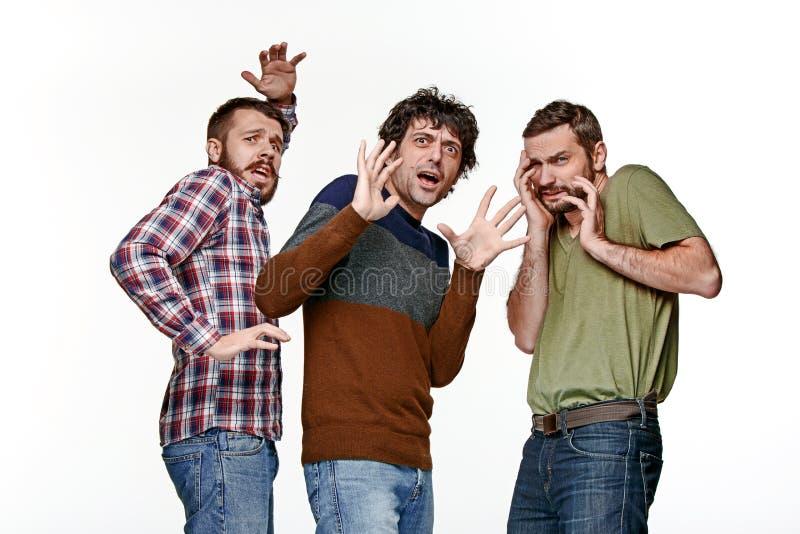 Los tres asustaron a los hombres jovenes que miraban la cámara imagen de archivo