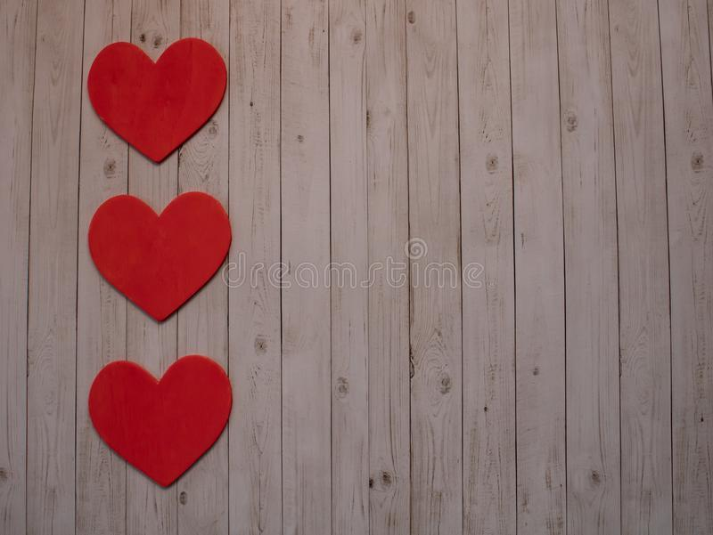 Los tres corazones de la tarjeta del día de San Valentín roja en fondo imagen de archivo