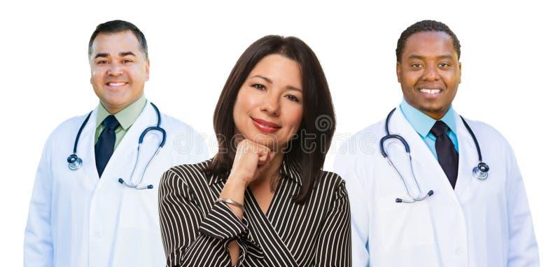 Los tres doctores Behind Hispanic Woman de la raza mixta en blanco imagenes de archivo