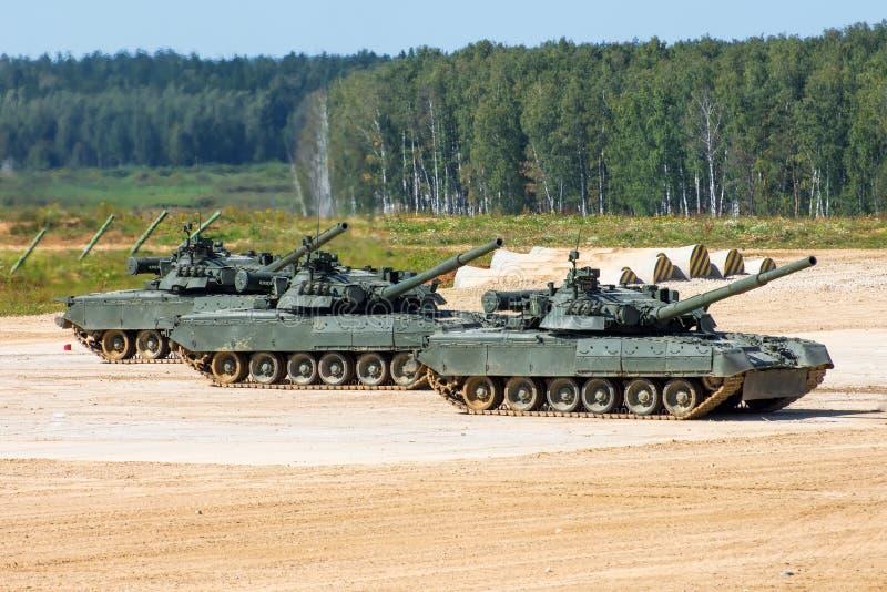 Los tres tanques militares se colocan en el campo con los bozales aumentados en el cielo imágenes de archivo libres de regalías