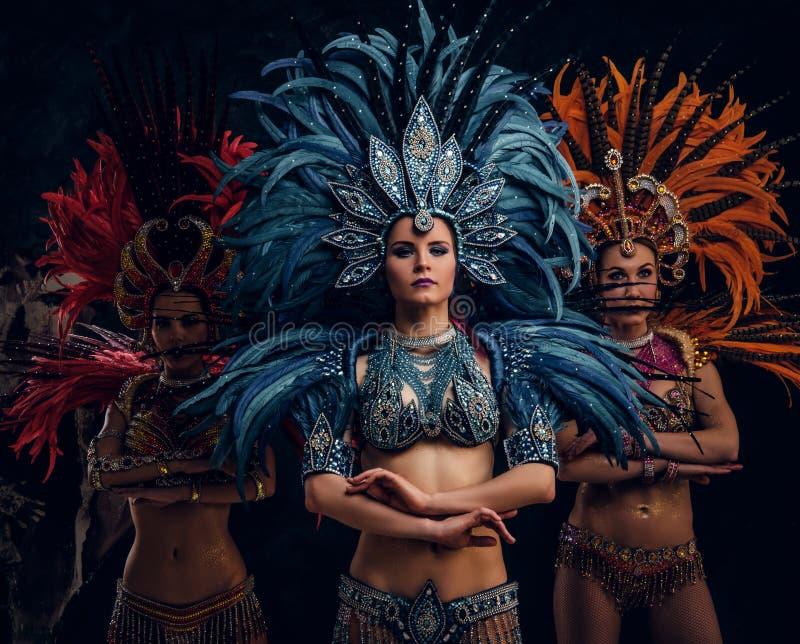 Los tres trajes carnaval brasile?os tradicionales de la mujer hermosa adentro est?n presentando para el fot?grafo en el estudio fotos de archivo