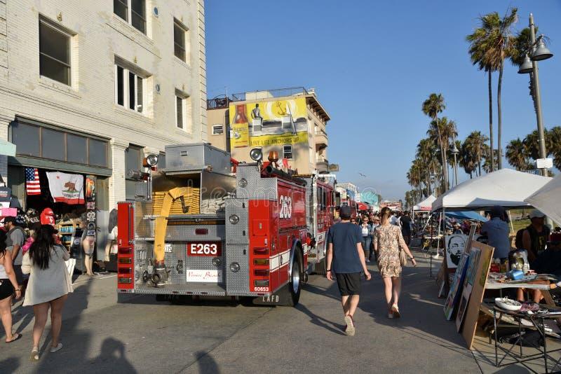 Los turistas caminan alrededor de los coches de bomberos en el paseo marítimo de Venecia imagenes de archivo