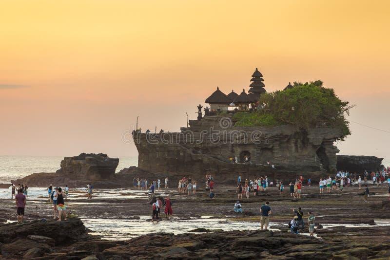 Los turistas caminan cerca del templo de la porción de Tanah durante puesta del sol en Bali fotos de archivo