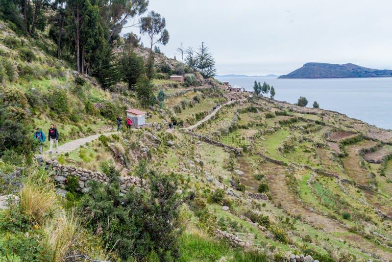 Los turistas caminan en una trayectoria en la isla de Taquile fotografía de archivo