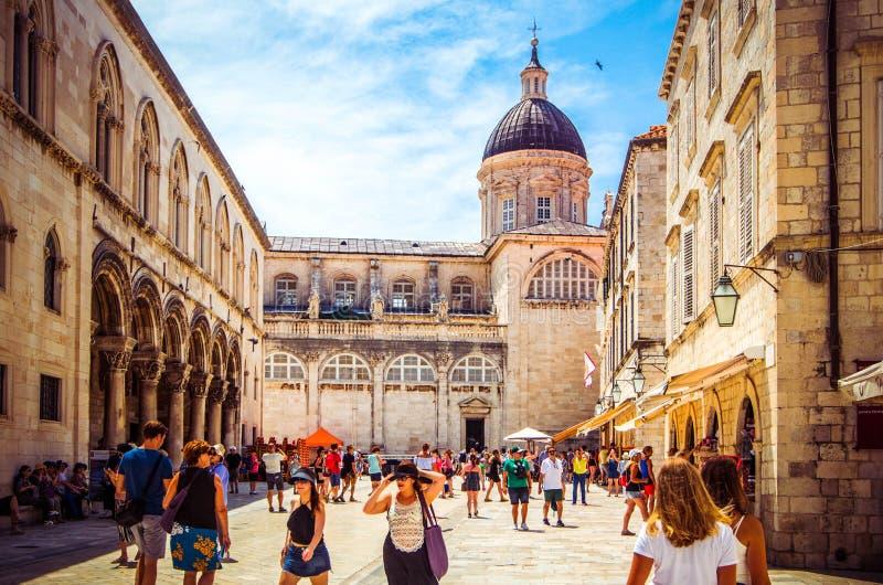 Los turistas caminan a lo largo de las calles de piedra pavimentadas de la ciudad vieja de Dubrovnik en día soleado caliente, Dub fotos de archivo