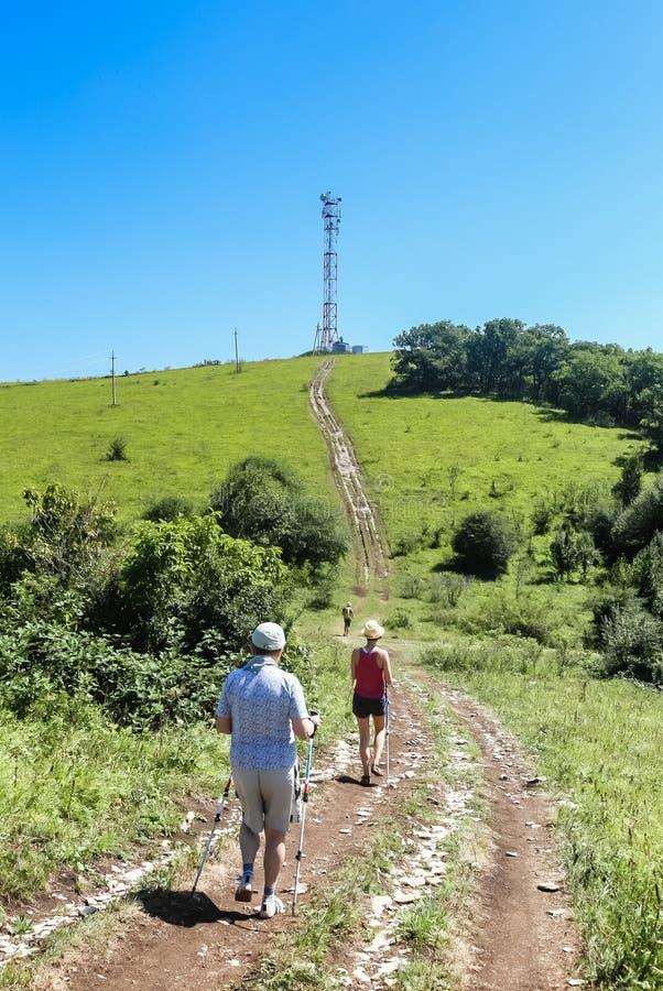 Los turistas caminan a lo largo del camino a la torre de comunicaciones encima de a imágenes de archivo libres de regalías