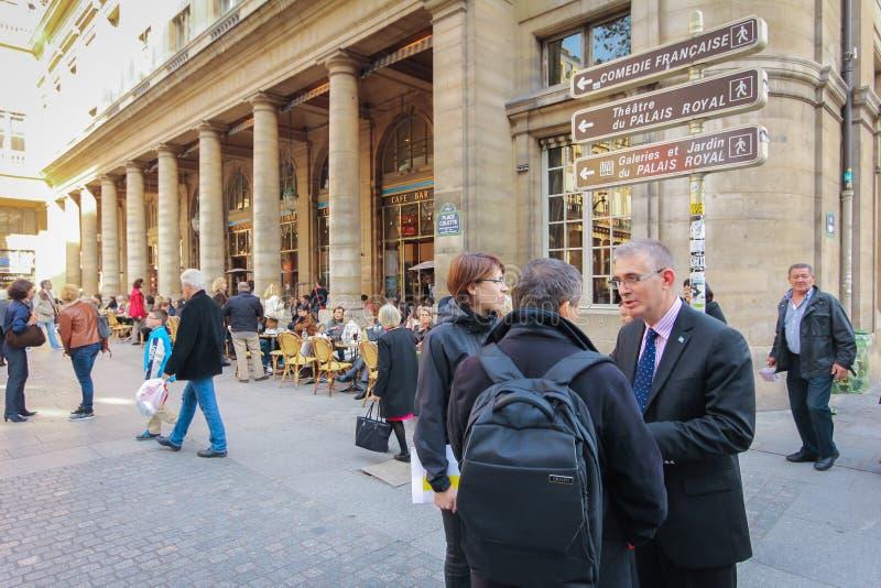 Los turistas caminan más allá de una cafetería y de una tienda del recuerdo en París jpg imagen de archivo libre de regalías