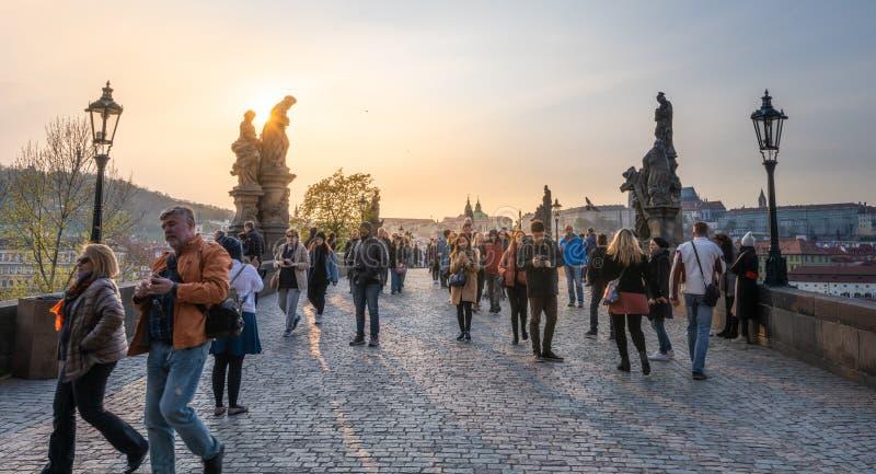Los turistas cruzan a Charles Bridge famoso en el capital en una tarde brillante de la puesta del sol imágenes de archivo libres de regalías