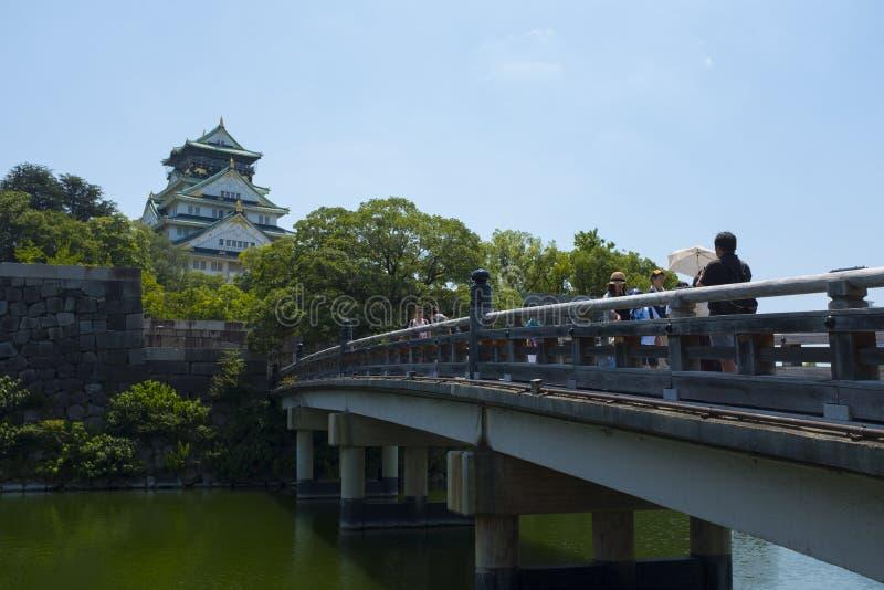 Los turistas cruzan el puente a Osaka Castle imágenes de archivo libres de regalías
