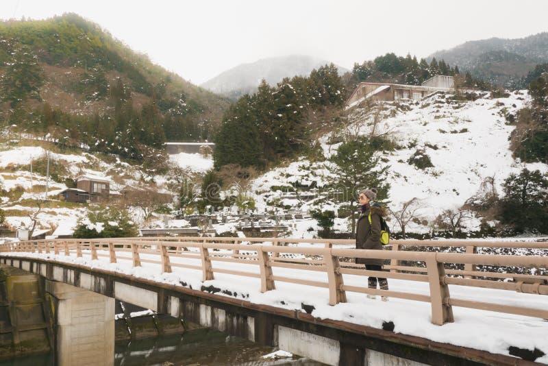 Los turistas de la muchacha aprecian la belleza natural del río, que se cubre con nieve Mientras que viaja al tsuwano foto de archivo