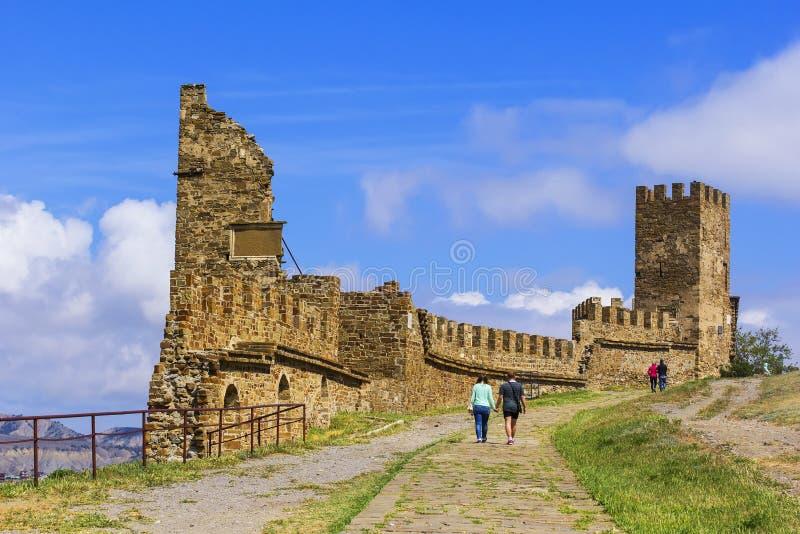 Los turistas de la opinión del paisaje del fondo caminan en una fortaleza de Sudak en medio de las ruinas de torres antiguas en l imágenes de archivo libres de regalías