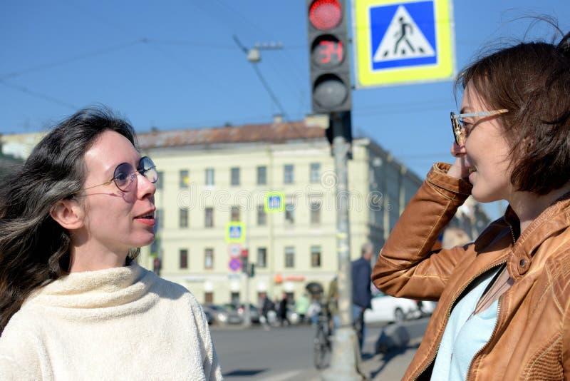 Los turistas de las se?oras jovenes tienen una parada en un puente en St Petersburg, Rusia y discutir la visita tur?stica de excu imágenes de archivo libres de regalías