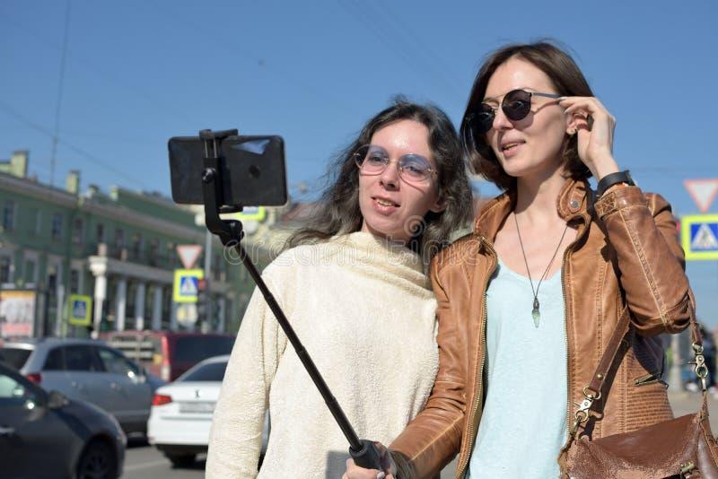 Los turistas de las se?oras jovenes hacen selfies en un puente en St Petersburg, Rusia, y se divierten delante de la c?mara foto de archivo libre de regalías