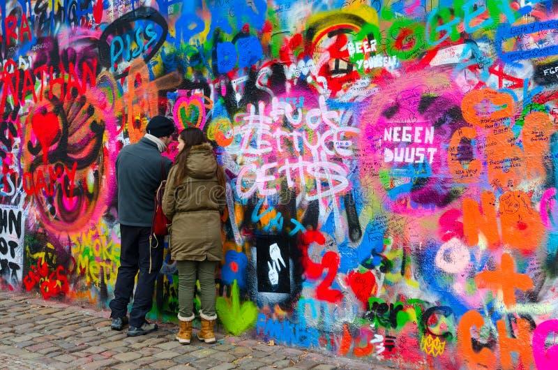 Los turistas dejan la inscripción en John Lennon Wall famoso en Praga, República Checa foto de archivo libre de regalías