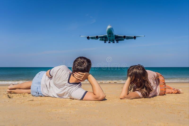 Los turistas del hombre y de la mujer se divierten en la playa que miran los aviones de aterrizaje El viajar en un concepto del a imagen de archivo libre de regalías