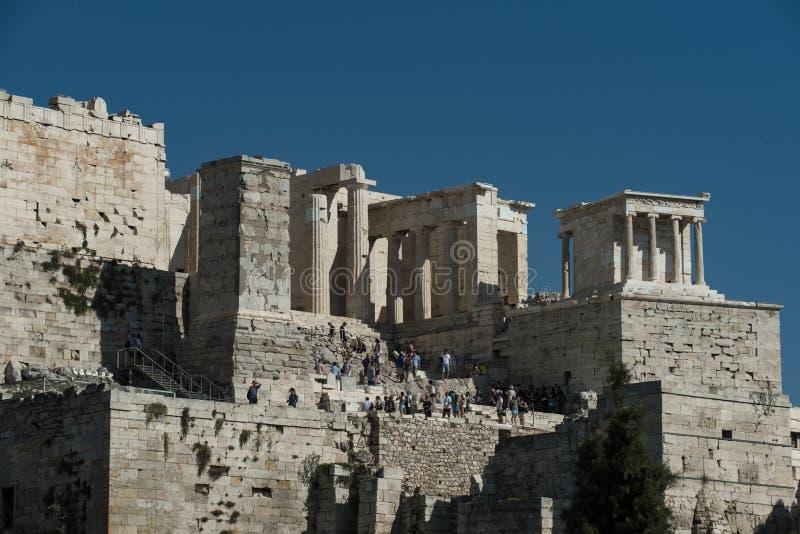 Los turistas descubren los restos del templo antiguo en la colina Gente en ruinas de la piedra en el cielo azul soleado El viajar fotografía de archivo