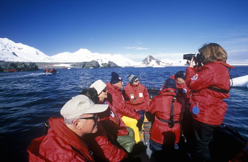 Los turistas ecológicos del barco de cruceros Marco Polo en barco inflable del zodiaco en el paraíso se abrigan, la Antártida fotos de archivo