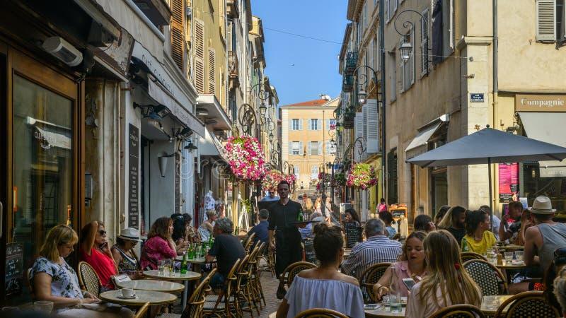 Los turistas en Antibes, ` Azur, Francia de Cote d se sientan en una terraza en un restaurante durante el verano imagen de archivo