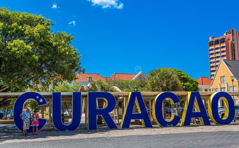 Los turistas en Curaçao azul firman adentro Willemstad foto de archivo libre de regalías