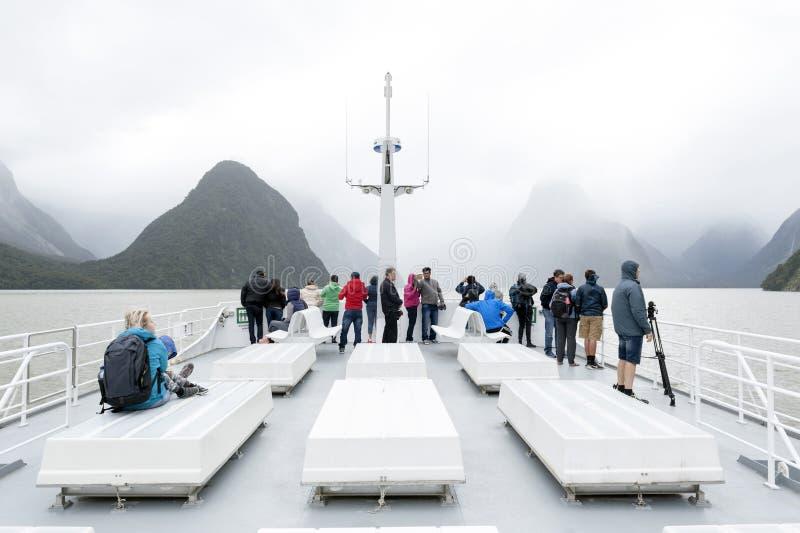 Los turistas en el barco cruzan en el fiordo de Milford Sound, isla del sur de Nueva Zelanda imagen de archivo libre de regalías
